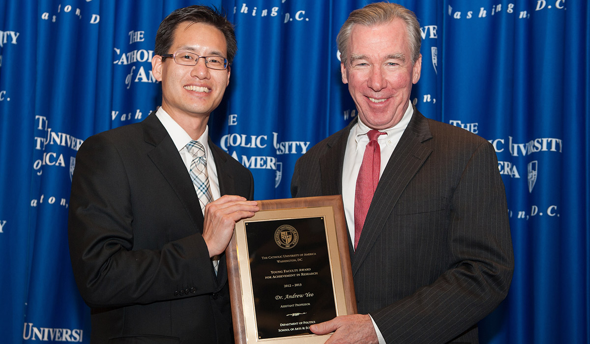Dr. Andrew Yeo being given an award by University President John Garvey